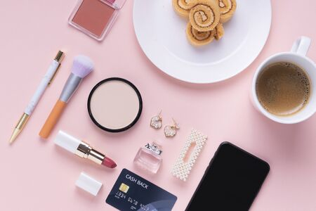 Top view - Cosmetic make up tools and dessert roll with coffee cup and smartphone with credit card over pink background. Archivio Fotografico