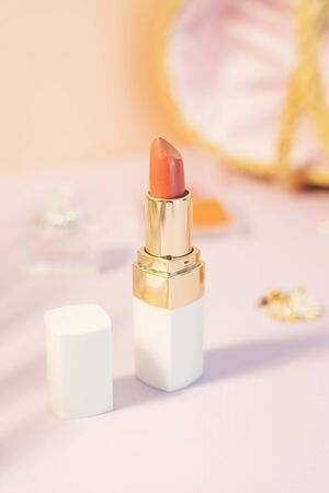 Commercial product - Orange tone lipstick in gloss white box over pastel background.