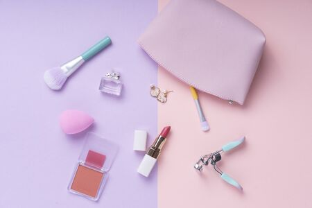 Cosmetics top view on pastel pink and purple table. Workplace and cosmetic bag.