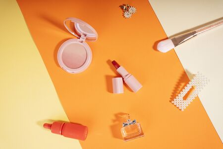 Woman accessories cosmetic background on orange background.