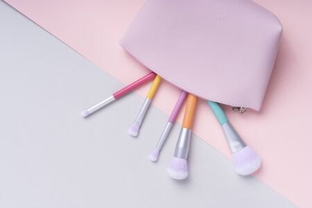 Top view - Colourful rainbow pastel brushes in pink bag over bright pink and blue background. Archivio Fotografico