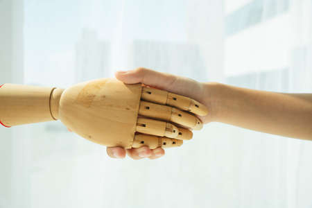 Hand of wooden cyborg robot and human shaking hand.