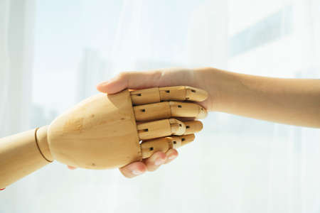 Hand of wooden cyborg robot and human shaking hand. 免版税图像 - 150641871