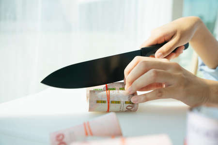 Cut cost concept. Business owner saving cost from using knife slicing banknote. Фото со стока