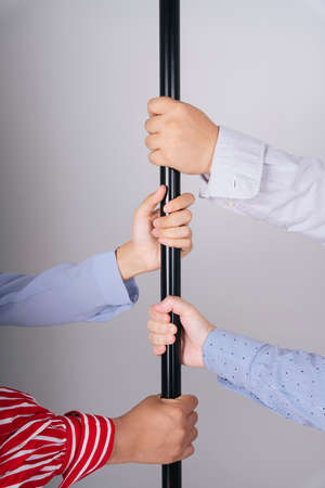 People hands grabbing a pole in a train isolate over white background.