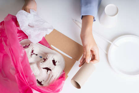 Woman hand clean up food package waste into plastic bag for recycle procedure. 写真素材 - 150641795