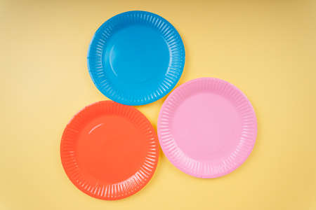 Four colourful plastic plate dishes over yellow beige background. Orange. Blue. Pink. 免版税图像