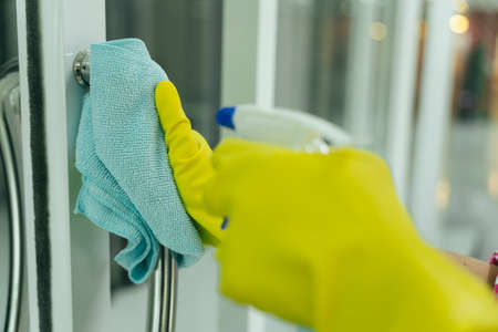 Maid wearing yellow protective gloves cleaning door entrance with rag and detergent spray bottle. Covid-19 Coronavirus prevention. Stok Fotoğraf