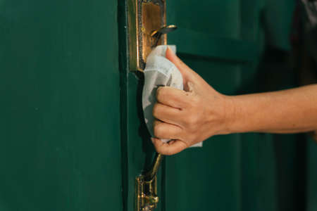 Woman hand cleaning door knob with tissue paper. Covid-19 Coronavirus prevention