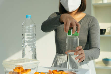 Woman wearing white mask pouring water from bottle in kitchen. Stok Fotoğraf