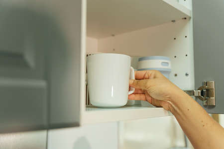 Woman hand picking up ceramic mug cup from shelf in kitchen. Stockfoto