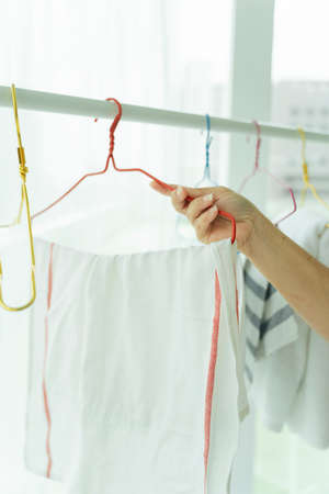 Maid woman hanging cloth after laundry on a rack. Stockfoto