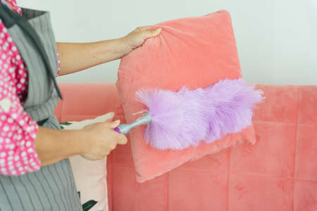 Maid cleaning sofa pillow couch with whisk broom shuttlecock in living room. Covid-19 Coronavirus prevention. Stock Photo