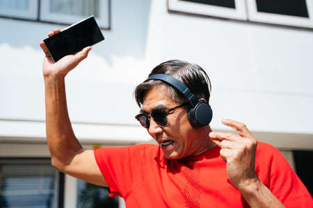 Old man in red t-shirt enjoy the music from mobile application in sunny day at his home.