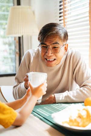 Grandpa and grandson hit the glasses of milk during their breakfast. Reklamní fotografie