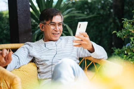 Old man wearing the earphone and listen the music from the application on smartphone.