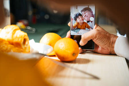 Grandpa and grandson in the camera of smartphone while they take a selfie together during breakfast. 写真素材