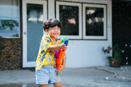 Little boy splash the water with water gun and rubber tube at his house in Songkran day, the yearly traditional day of Thailand.