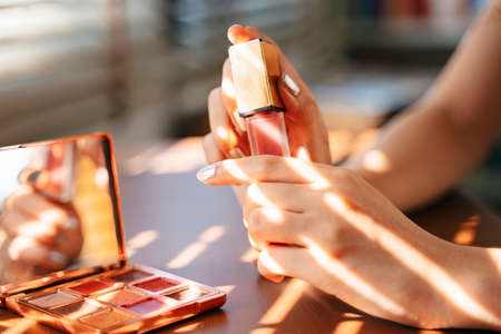 Cropped image of pink lipstick in woman's hands at the table with sunlight through the louver.