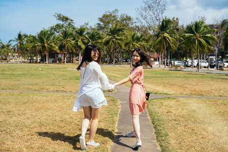 Two girls hold each other hands while walking and playing in the grass field in sunshine of summer. 免版税图像