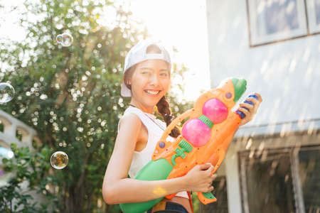 Beautigul woman splash the water with water gun in Songkran day, splashed water and bubble.
