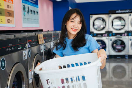 Cute girl standing and holding white basket in front of washing machine.