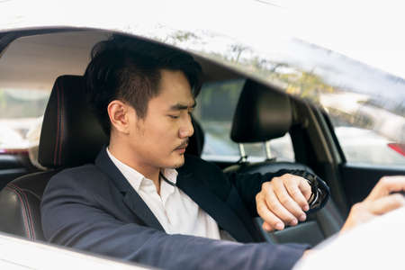 Dangerous situation - Asian thai businessman on formal suit using mobile phone while driving a car on the road. 免版税图像 - 151105564