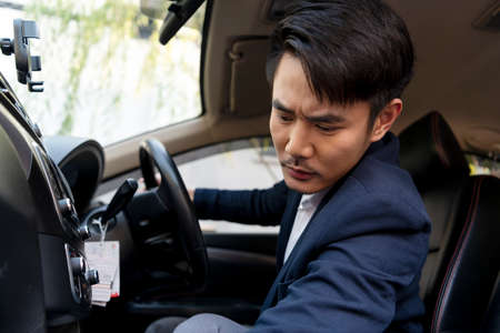 Dangerous situation - Asian thai businessman on formal suit using mobile phone while driving a car on the road. 免版税图像 - 151105297