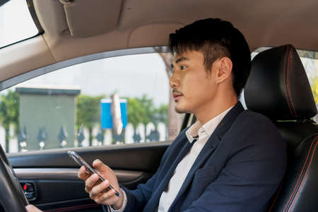 Dangerous situation - Asian thai businessman on formal suit using mobile phone while driving a car on the road. 免版税图像 - 151105341