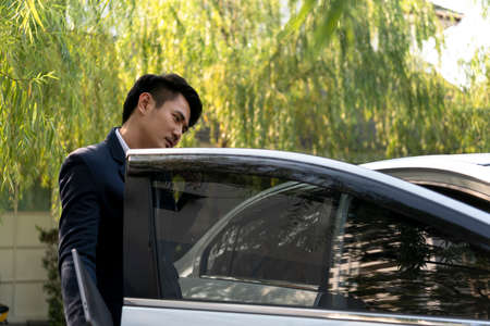 Busy asian thai businessman on formal suit holding laptop and talking on the phone at the car.