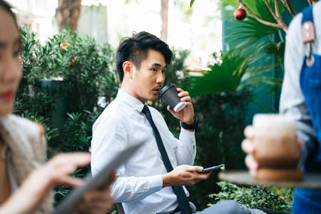 Smart asian business people on formal shirt drinking coffee from a cup at coffee shop. Stock fotó