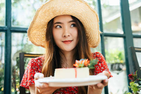 Close up portrait Young asian thai woman on red dress wearing hat holding a cheesecake plate. Dessert lover.