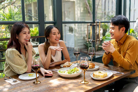 Asian thai people enjoy having food together in the restaurant. People eating food at lunch time on table with wine.