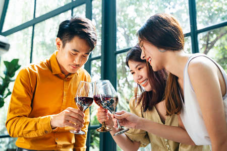 Group of young asian thai people enjoy drinking red wine toasting and celebrating. 免版税图像