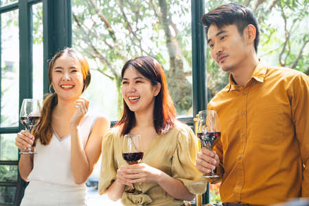Cheerful three asian thai people having fun at party. Holding glasses of wine at restaurant. 免版税图像
