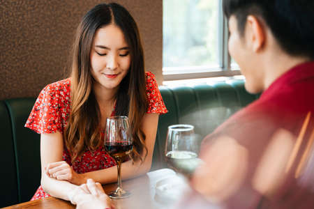 Cheerful three asian thai people having fun at party. Holding glasses of wine at restaurant. Stock fotó