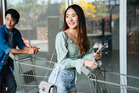 Asian people walking with cart trolley in shopping mall. Stock Photo