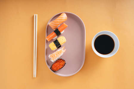 Top view - Japanese Shushi on a plate with shoyu soy sauce and chop stick.