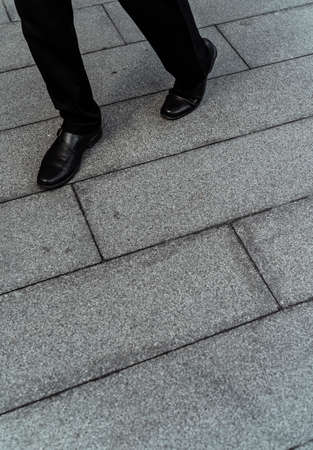 Low section shot of man wear cut shoes walking on pavement floor.