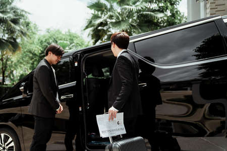 Confident asian driver standing by car, security guard service. Chauffeur man opening car door for businessman. Business trip by a car.