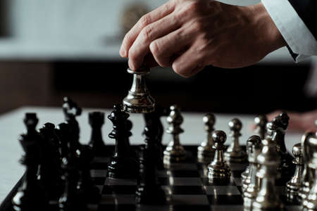 hand of businessman moving chess figure in competition success play. strategy, management or leadership concept. Hand of confident businessman use king chess piece silver playing chess game to crash overthrow the opposite team and development analysis new strategy plan, business strategy for win and success.