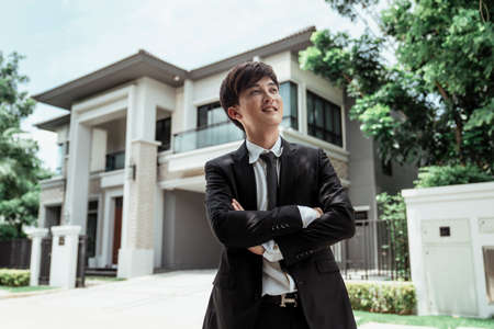 Portrait of asian successful businessman with a big house at background. Rich guy with gigantic house.