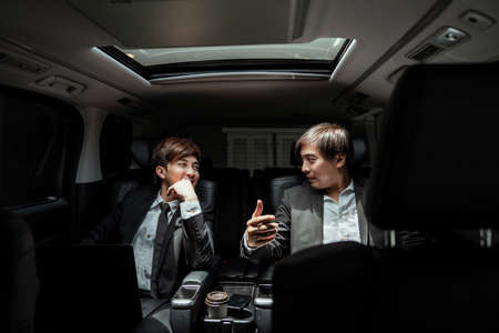 Two asian businessmen having conversation, talking, discussing about company strategy plan in a car. Standard-Bild