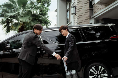 Confident asian driver standing by car, security guard service. Chauffeur man opening car door for businessman. Business trip by a car. helping his boss carry the luggage.