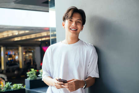 Teenager guy in white t-shirt leaning againt the building's pole using his mobile phone and smile.