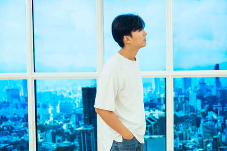 Teenage guy in jeans and white t-shirt standing next to the glasses window on high building.