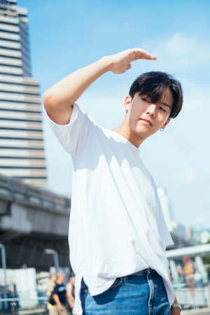 Low angle shot of teenage guy in white t-shirt standing in the sunlight raise his hand protect his eyes with coll posture, vertical.