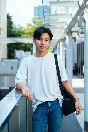 Black hair teenage guy in jeans and white t-shirt prop his elbow on glasses barricade while chilling at the terrace. Imagens
