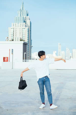 Teenage guy in jeans and white t-shirt standing with spreaded arms on the rooftoop of high building in the city.
