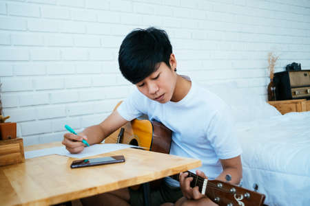 Black hair musician guy sitting at the wooden table in his bedroom and create his own song with guitar.